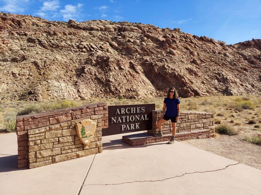 kara at arches national park entrance sign