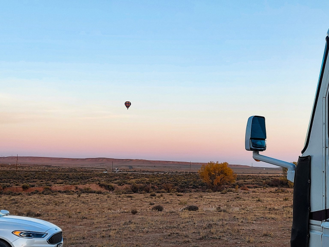 Campsite view of hot air balloon over airport near Moab National Parks
