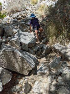 kara climbing over boulders on maidenhair falls trail in anza borrego