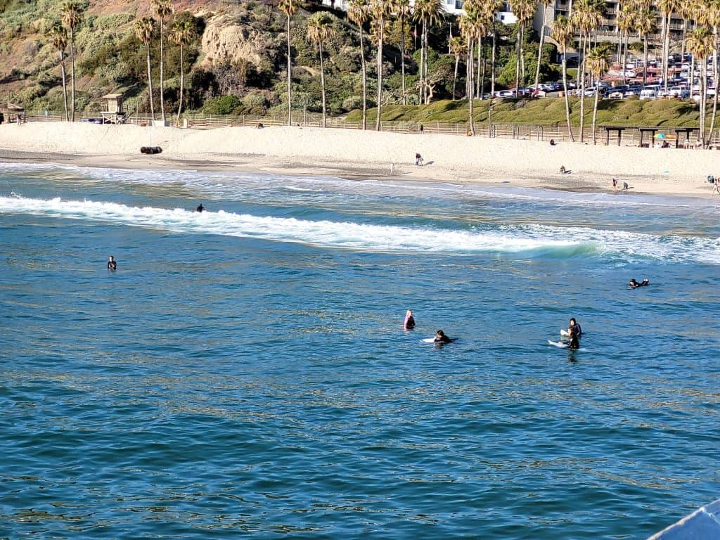 surfers at the san clemente beach from the pier